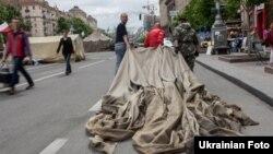 Активисты Майдана уносят в площади разобранную палатку. Киев, 28 мая 2014 года.