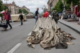 Майдан белсенділері алаңнан жинап алынған шатырды әкетіп барады. Киев, 28 мамыр 2014 жыл.