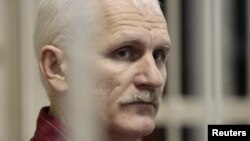 Belarusian human rights activist Ales Byalyatski sits in a guarded cage in a courtroom in Minsk during his trial in November 2011.