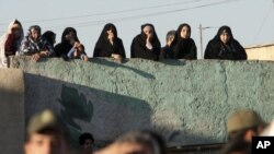 People watch an execution of a convicted man in the Iranian city of Qazvin in May