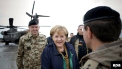 German Chancellor Angela Merkel is welcomed by officers of the German armed forces in Kundus.