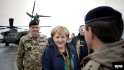 Germaniýanyň kansleri Angela Merkel Gunduzdaky german ýaragly güýçleriniň ofiseri tarapyndan garşy alynýar, 6-njy aprel, 2009 ý.