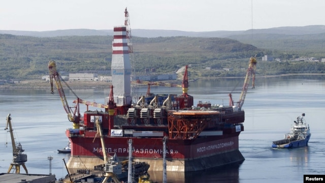 A floating oil platform is tugged from the harbor in the northern Russian port of Murmansk.