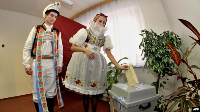 People wearing traditional costumes cast their votes at a polling station in Strazovice, in south Moravia.