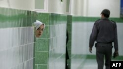 A female inmate peers from behind a wall in the female section of Evin prison. (file photo)