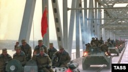 A column of Soviet military vehicles crosses returns from Afghanistan in February 1989. But Soviet contributions to Afghanistan still remain. Will U.S. contributions fare as well?
