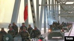 FILE: A column of Soviet military vehicles crosses the border in Termez, Uzbekistan as they return from Afghanistan (February 1989).
