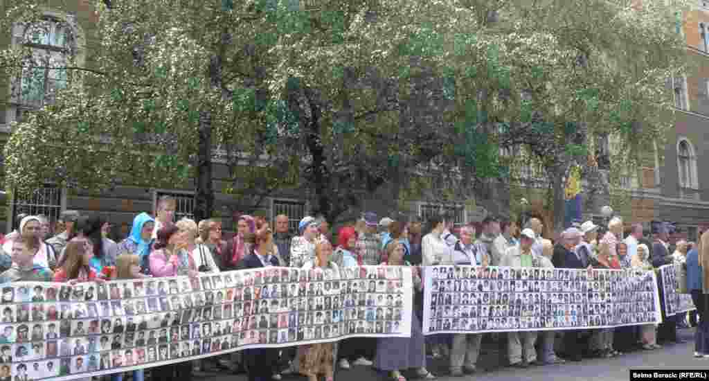 People hold a placard with portraits of people killed in the 1995 Srebrenica massacre.