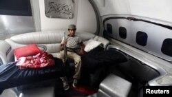 Либиски бунтовник сликан во авионот на убиениот диктатор Моамер Гадафи на аеродромот во Триполи на 28 август 2011 година.