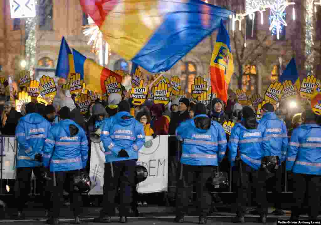 """People shout while holding signs that read """"All For Justice"""" outside the government headquarters in Bucharest. More than 10,000 people on December 10 participated in another round of protests against Romanian legislation that critics say would make it harder to punish high-level corruption. (AP/Vadim Ghirda)"""