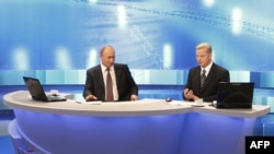 Russian Prime Minister Vladimir Putin (left) answers questions during a nationally televised town-hall-style session in Moscow.