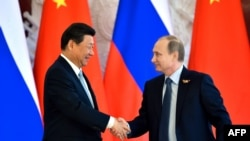 Russian President Vladimir Putin (right) shakes hands with his Chinese counterpart Xi Jinping in Moscow on May 8.