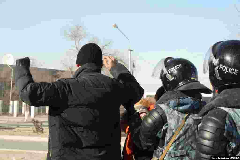 Жаңаөзен көшесінде кездескен адамды полиция тексеріп жатыр. Маңғыстау облысы, 19 желтоқсан 2011 жыл.