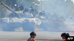 GEORGIA -- Russian tanks move along a street as children play with a toy truck in Tskhinvali, the capital of South Ossetia, 30Aug2008.