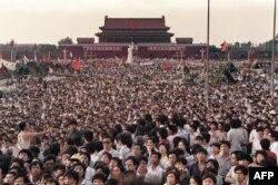 Chinese people gather around a replica of the Statue of Liberty on Tiananmen Square demanding democracy despite martial law in Beijing in June 1989.