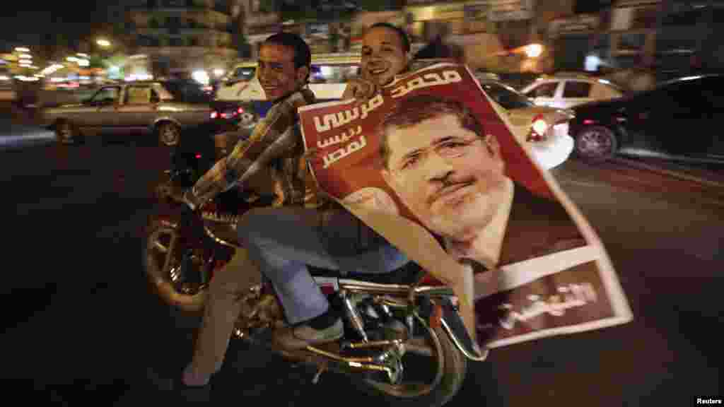 Supporters of newly elected Egyptian President Muhammad Morsi hold up his poster as they celebrate while riding a motorbike on Tahrir Square in Cairo on July 9. (REUTERS/Amr Abdallah Dalsh)