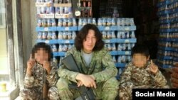 Kazakh IS militant Artyom Avdeyev poses with what he says are two Kyrgyz boys in an image he later deleted from his account.