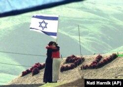 دو دختر نوجوان اسرائیلی در یادبود هفت همکلاسی خود که به ضرب گلوله سرباز اردنی کشته شدند، یکدیگر را در آغوش کشیدهاند/ دوم مارس ۱۹۹۸