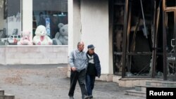 NAGORNO-KARABAKH -- Men walk past a burnt shop in Stepanakert, November 16, 2020