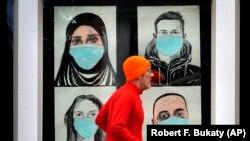 Бегущий на фоне плаката с изображением людей в защитных масках человек. Льюистон (штат Мэн), 16 ноября 2020 года.