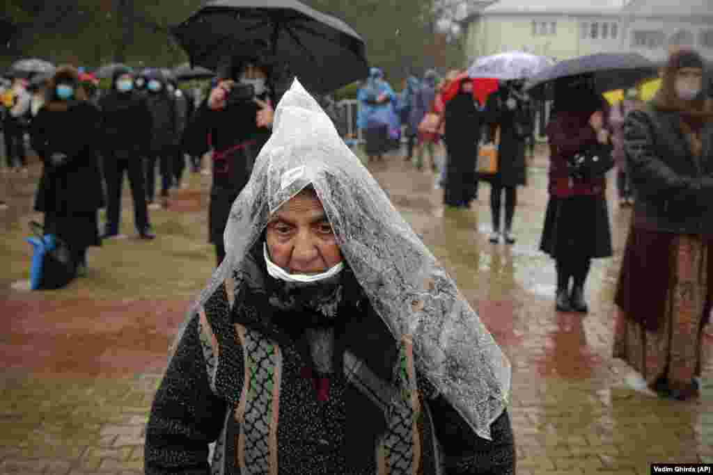 A woman uses a plastic sheet as rain protection as she attends a religious service celebrating St. Andrew in the village of Ion Corvin in eastern Romania. Braving wintry weather and coronavirus fears, several hundred Orthodox Christian believers gathered outside a cave in eastern Romania where St. Andrew is said to have lived and preached in the first century. (AP/Vadim Ghirda)