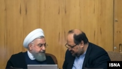 President Hassan Rouhani (left) is speaking with minister of industry, Mohammad Shariatmadari, in the cabinet session, June 27, 2018.