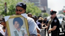 A man holds a portrait of a young Michael Jackson as he and other people wait in line for a public memorial for the late pop icon in New York in June.