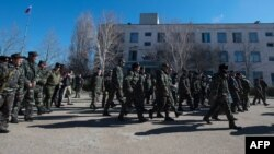 Ukrainian soldiers walk out of a Ukrainian air force base in the small Crimean city of Novofedorivka after it was stormed by pro-Russian protesters on March 22.