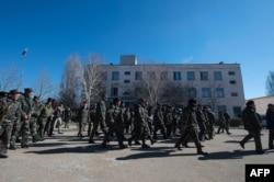 Українські військові залишають частину в селищі Новофедорівка після штурму проросійськими протестувальниками, 22 березня 2014 року
