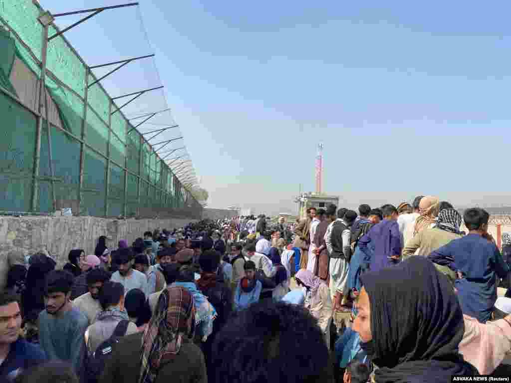 Мясцовыя жыхары, якія імкнуцца пакінуць Афганістан, днямі чакаюць ля аэрапорту.