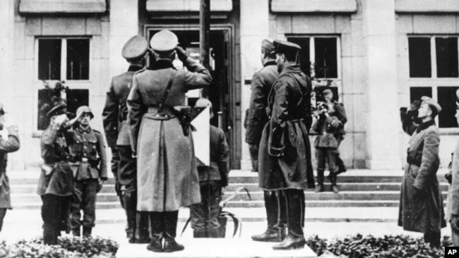 Немецкие и советские офицеры отдают салют флагу с нацистской свастикой во время парада в Брест-Литовске по случаю демаркации границы в Польше, 22 сентября 1939 года