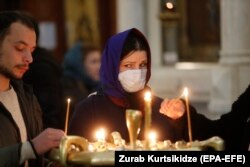 Georgian Orthodox believers light candles during a religious service in Tbilisi earlier this month.
