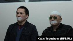 Подсудимые по делу «джихадистов» — Алмат Жумагулов (слева) и Оралбек Омыров, — заявившие отвод прокурору и объявившие бойкот суду, и в знак этого заклеившие себе рот бумажным скотчем. Алматы, 15 октября 2018 года.