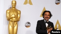 """Birdman"" director Alejandro Inarritu poses with the Oscars for best director, best original screenplay, and best picture."