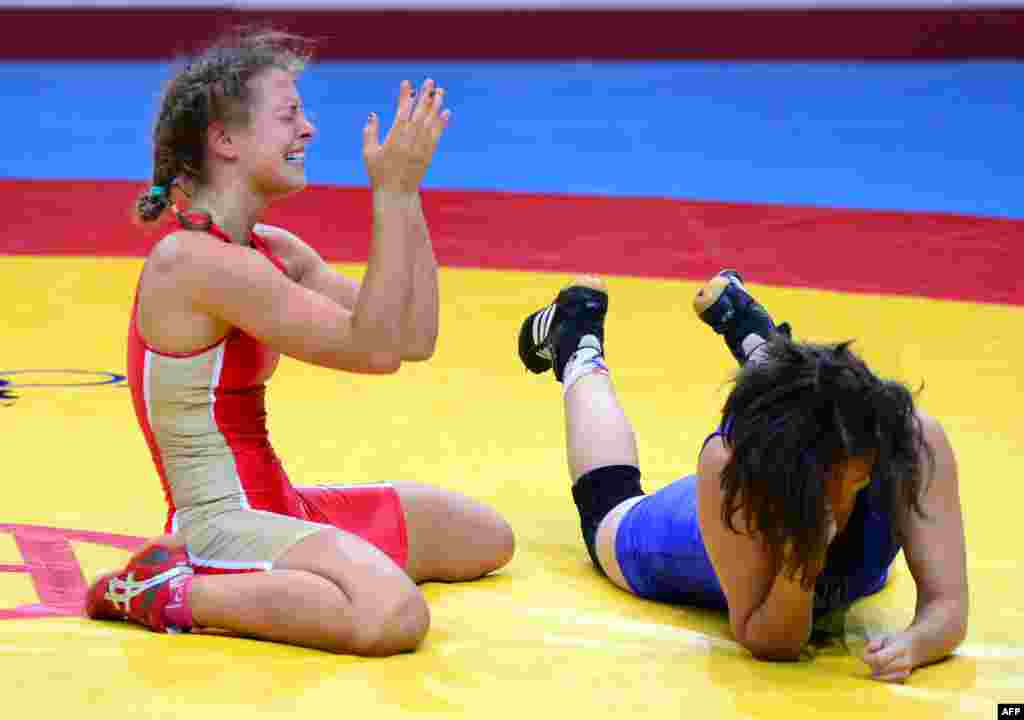 Russia's Valeria Koblova (left) celebrates her victory over Ukraine's Iryna Husyak during the women's freestyle 55-kilogram category for bronze of the FILA World Wrestling Championships in Budapest. (AFP/Attila Kisbenedek)