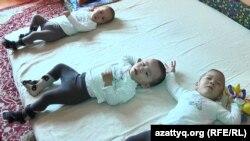 Тройняшки с ДЦП лежат на полу в квартире, где они живут. Город Капшагай Алматинской области, апрель 2017 года.