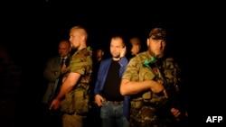 Александр Бородай (в центре), самопровозглашеннный премьер-министр так называемой Донецкой Народной Республики, говорит по телефону в окружении вооруженных соратников. Город Шахтарск Донецкой области. 17 июля 2014 года.