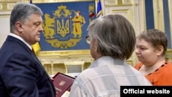 Ukrainian President Petro Poroshenko (left) presents the Hero of Ukraine medal to the parents of Mikhail Zhyzneuski in Kyiv on June 13.