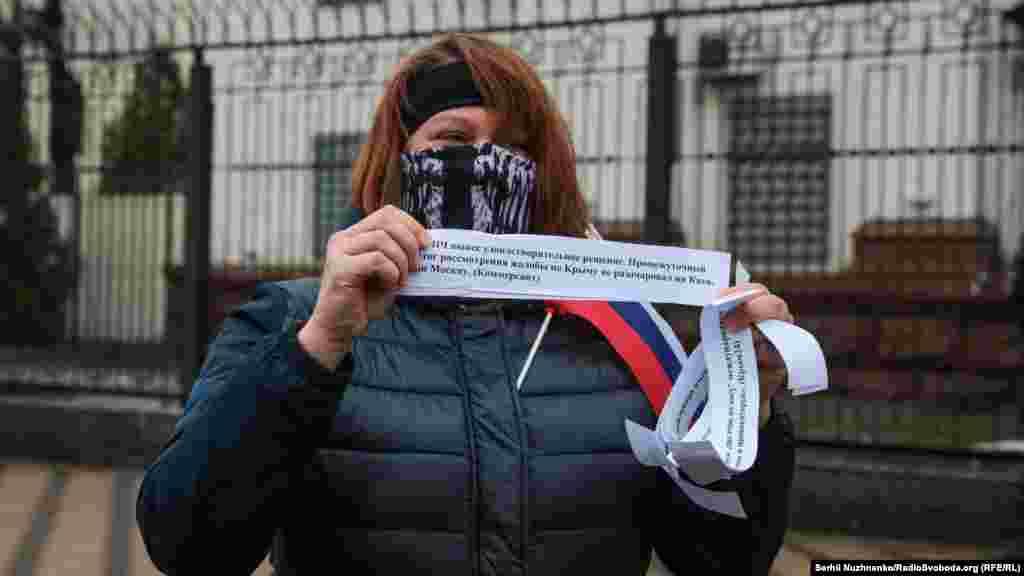 """Aktsiyanıñ iştirakçisi, """"Kommersant"""" rus neşrisinden kesip alınğan alıntınen parçanı tuta. Teşkilâtçılar bildireler ki, """"halqara mahkemeler Ukrainanıñ Rusiyege qarşı davalarını ne qadar çoq baqsalar da, netice bir olacaq – Rusiye, Rusiye akimiyet organlarınıñ tarafından ruhset etilgen cinayetleri, şu cümleden adam qaçırma ve öldürme içün cevap bermege mecbur olacaq""""."""