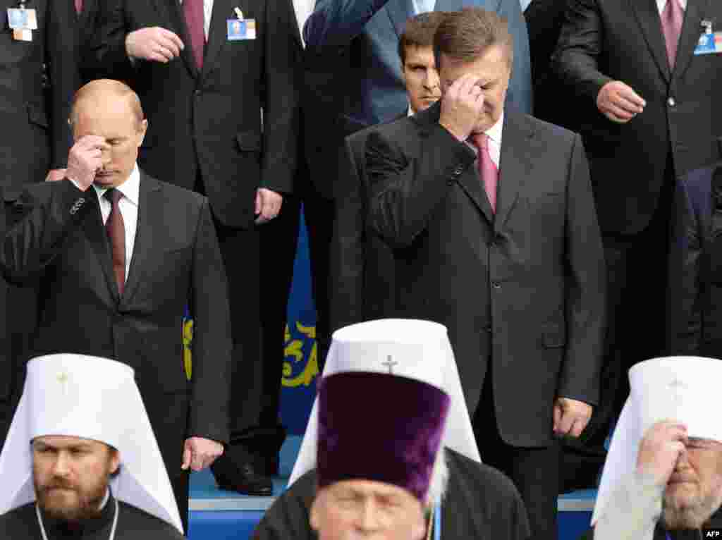 Russian President Vladimir Putin (left) and Ukrainian President Viktor Yanukovych cross themselves during a service and an official ceremony in Kyiv.