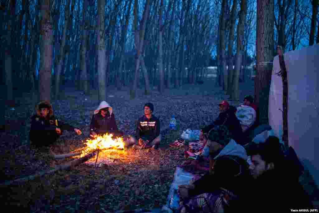 Группа мигрантов греется у огня в ожидании возможности пересечь реку Марицу на границе, 2 марта 2020 года.