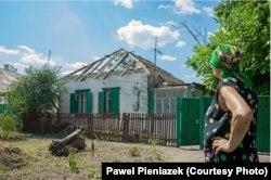 Іловайськ, жінка біля свого зруйнованого будинку. Фото: Павел Пеньонжек