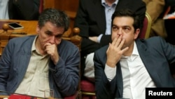 Greek Prime Minister Alexis Tsipras (right) sits next to Finance Minister Euclid Tsakalotos as he attends a parliamentary session in Athens on July 16.
