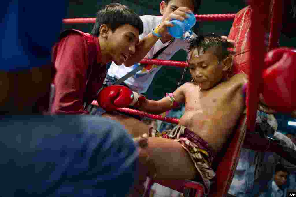 A young Muay Thai boxer resting and getting coached between rounds in his corner