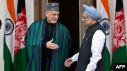 Afghan President Hamid Karzai (left) with Indian Prime Minister Manmohan Singh prior to delegation-level talks and an agreement-signing in New Delhi on November 12.