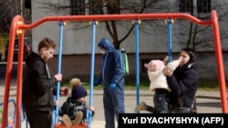 An employee wearing protective gear sprays disinfectant at a children's playground as a protective measure against the coronavirus in the western Ukrainian city of Lviv.