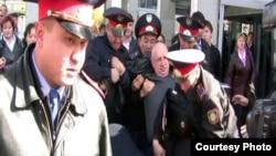 """Полиция тіркелмеген """"Алға"""" партиясының жетекшісі Владимир Козловты күштеп автобусқа әкетіп барады. Алматы, 14 қазан, 2009 жыл."""