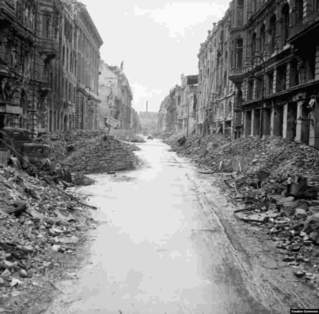 A car drives down a gutted Berlin street.   Much of the damage was from British, American, and French bombing raids that killed tens of thousands of civilians.