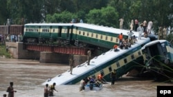 Security officials rescue passengers after train cars fell into a canal following the partial collapse of a bridge in Wazirabad in Punjab Province on July 2.