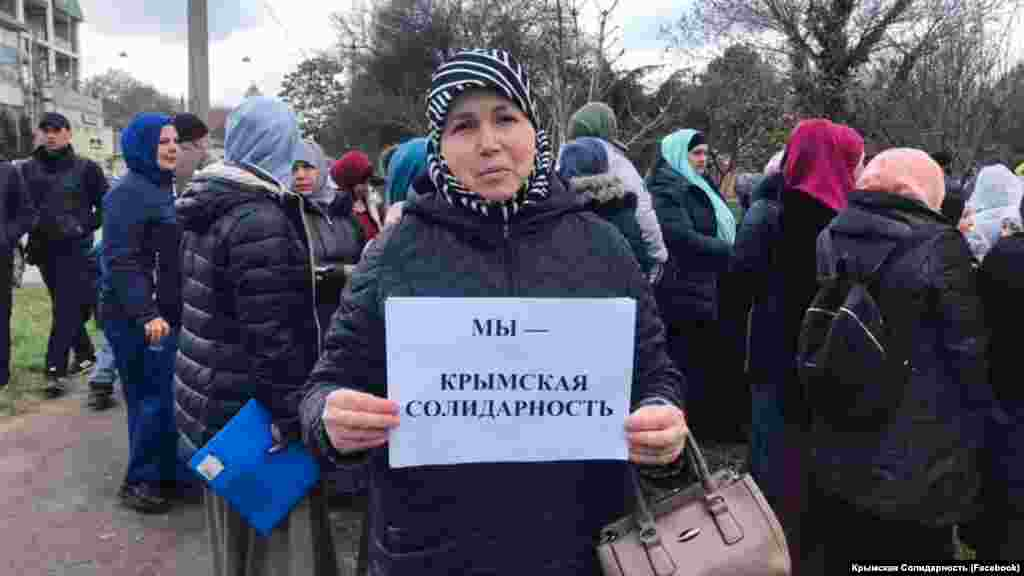 Дети и жены крымскотатарских активистов держат в руках листы бумаги с надписями «Мы – крымская солидарность» и «Верните 166-ти детям их отцов»